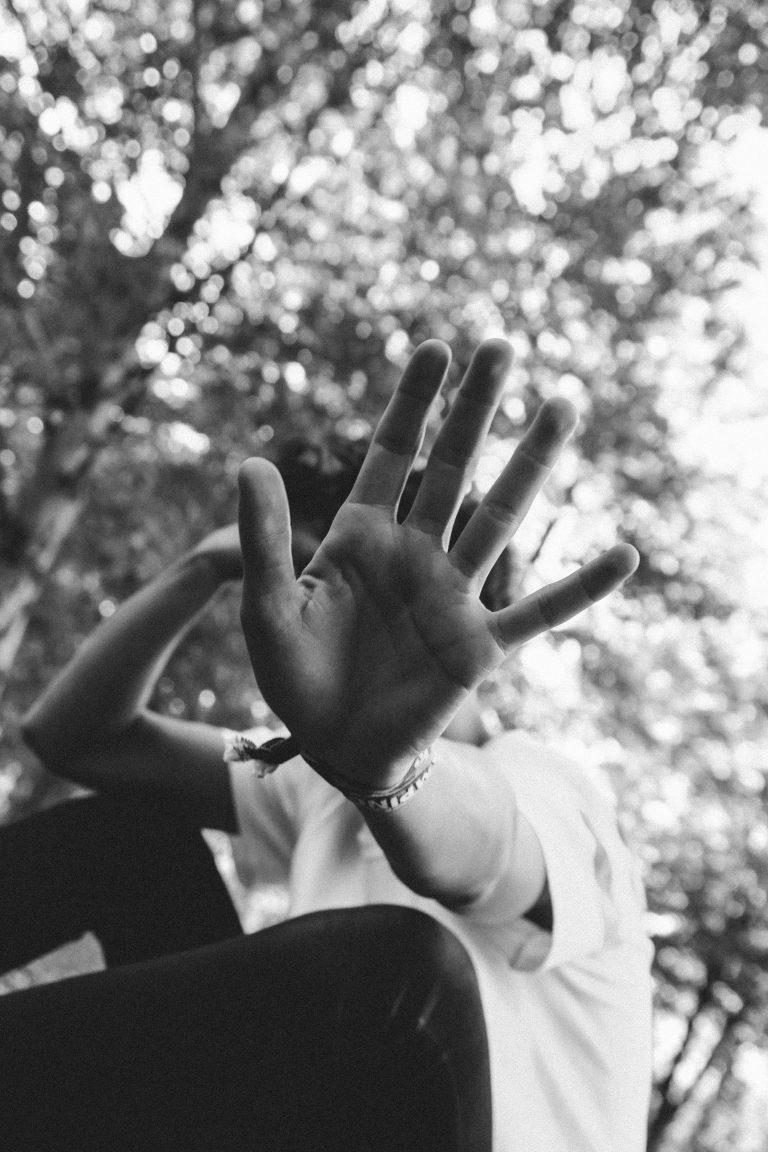 Eine junge Frau, die abwehrend die Hand vor sich hält